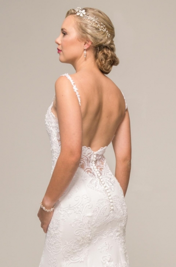 Off-white beaded lace dress in a sheath silhouette featuring a sweetheart neckline, thin lace straps, illusion low back, cathedral train, covered buttons and loops, stretch inner for a figure flattering fit.